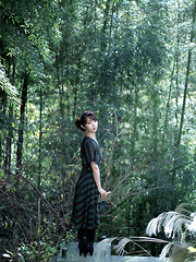 Neo Asian in long dress goes to enjoy reading book in the forest